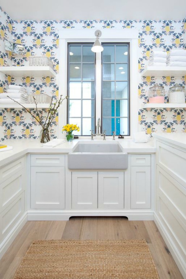 Farm sink, cheerful wallpaper, floating shelves, and white custom cabinetry in a butler pantry of a modern French home. #butlerpantry #floatingshelves #frenchcountry #farmsink