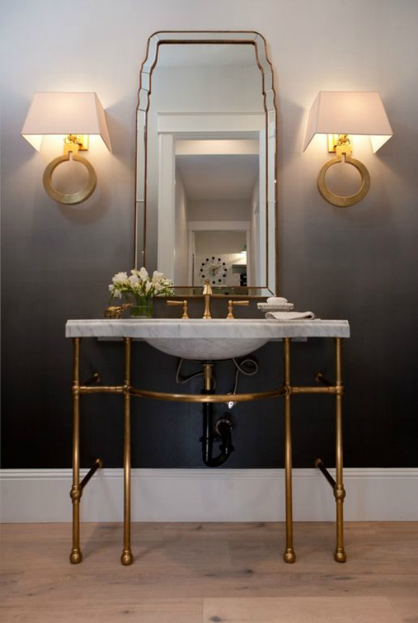 Elegant powder room with dark grey walls and wide vintage style console sink with brass hardware. #bathroomdesign #powderroom #consolesink #elegantdecor #interiordesign