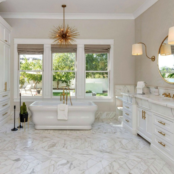 Luxurious bath design with marble, white cabinetry, and brass hardware in a modern French home in Queen Creek, AZ. #bathroomdesign #luxurious #whitemarble #modernFrench