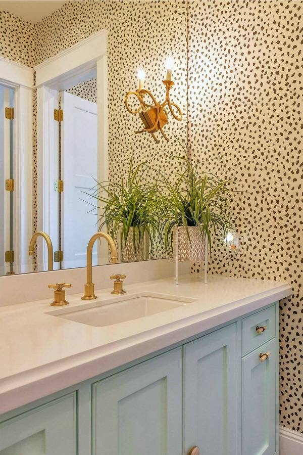Whimsical wallpaper in a contemporary bath with brass hardware. #bathroomdesign #wallpaper #brasshardware