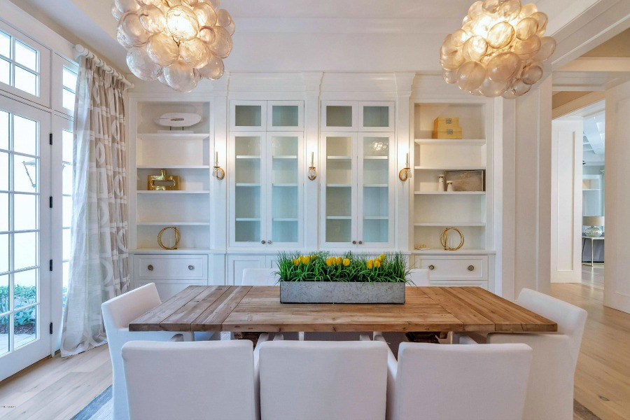 Modern French interior design in a dining room with contemporary pendants, built-ins, and a rustic dining table. #modernfrench #interiordesign #diningroom #builtins
