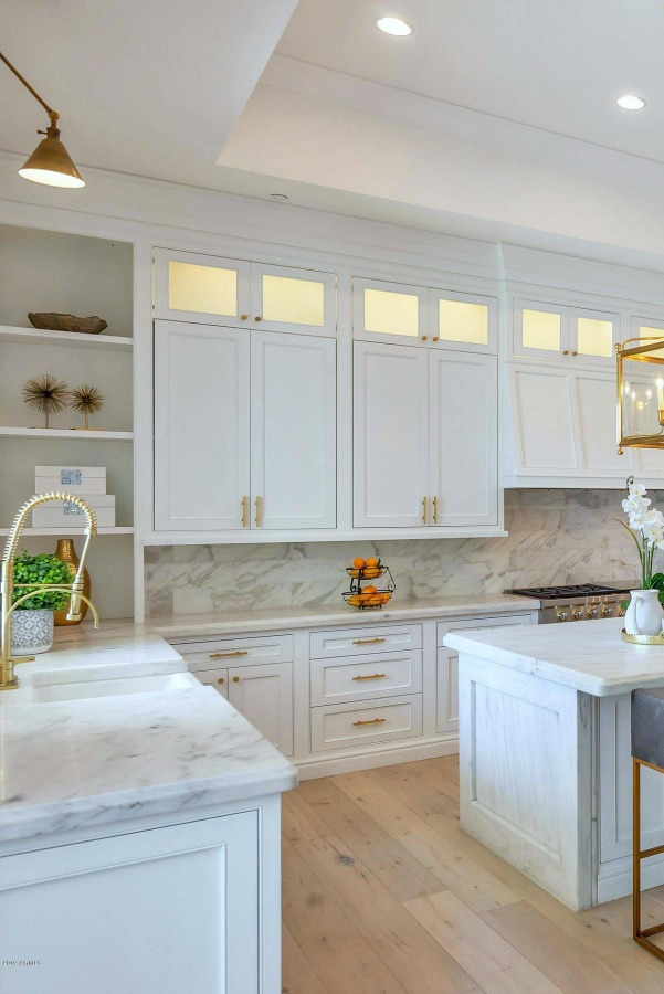 Breathtaking white kitchen with farm sink and large island with brass hardware in modern French home. #interiordesign #kitchendesign #modernfrench #whitekitchen