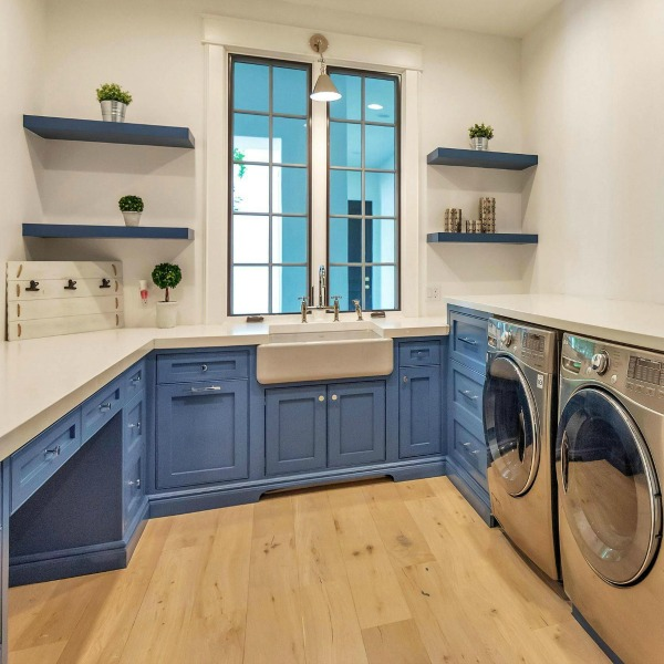 Modern French laundry room with bright blue painted cabinetry, floating shelves, and farm sink. #laundryroom #interiordesign #modernfrench #bluecabinets