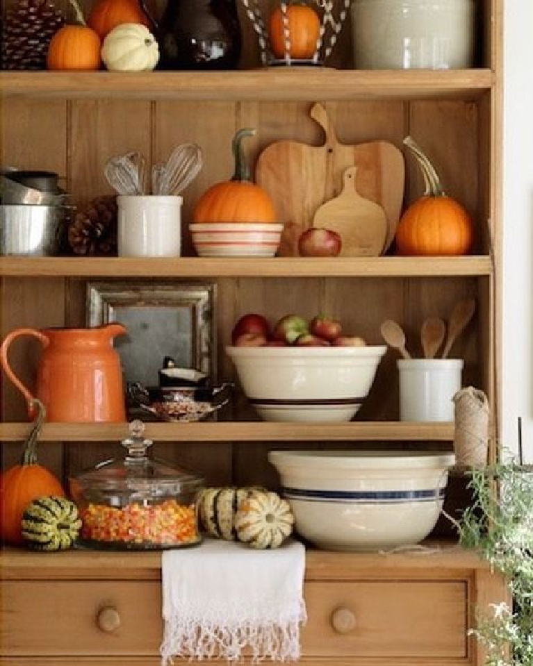 Come get Inspiring Autumn Feels From Instagrammers to Follow + Encouragement Quotes! Nora Murphy's contry cabinet and wood shelves with fall pumpkins, orange, and stoneware. #noramurphy #countrydecor #falldecor #farmhousefall