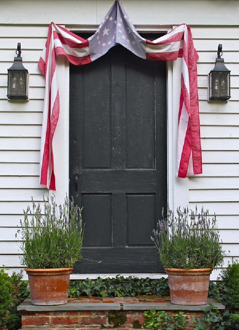 Nora Murphy's charming Connecticut farmhouse black door with faded American flag bunting and old lanterns flanking it. #noramurphy #farmhousedoor #4thofjuly #countryhouse #americana #countrystyle
