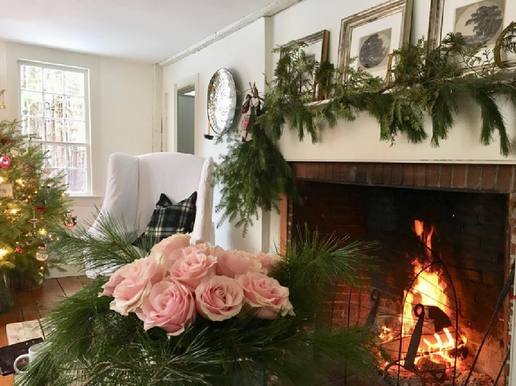 Nora Murphy's charming farmhouse living room with fireplace decorated for Christmas.