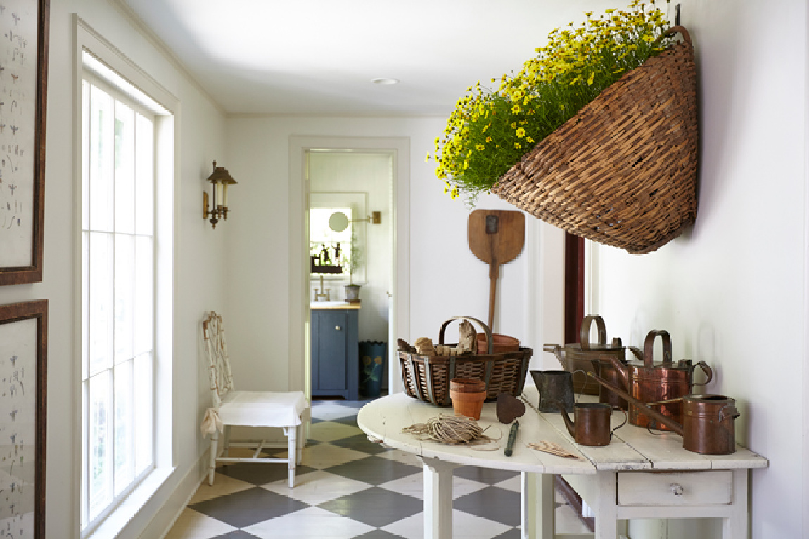 Nora Murphy's charming Connecticut farmhouse gallery with huge basket full of yellow flowers on wall.