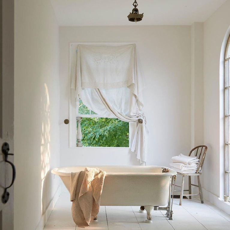 A charmingly serene white French country bath with white painted floors, clawfoot tub, magnificent naturallight and vintage textiles. Wendy Lewis design (Textile Trunk) featured in Nora Murphy's Country House book (Vendome Press).