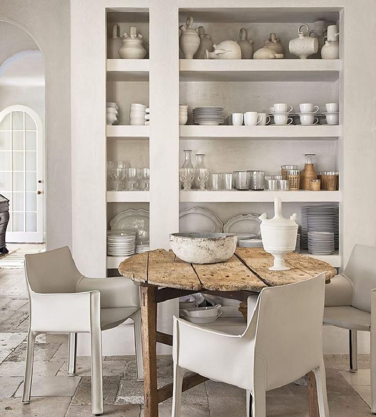 Breathtaking white modern French breakfast dining area with shelves, farm table, and modern chairs - interior design by Pamela Pierce. #pamelapierce #modernfrench #allwhitedecor #frenchcountry
