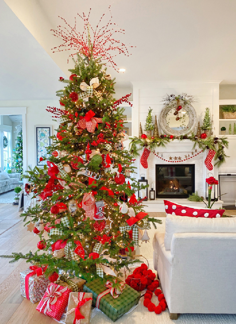 Vivid red accents on a cheerful Christmas tree in a whimsical family room decorated festively for the holidays - PlaidsandPoppies.