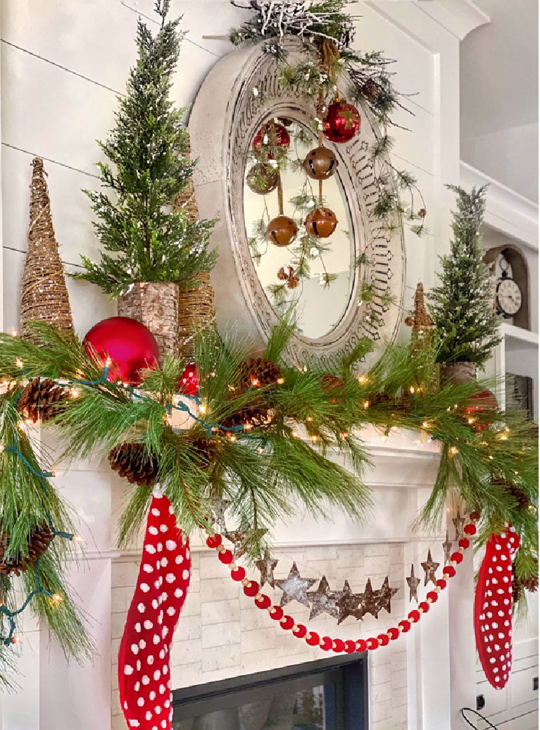 Merry and bright Christmas fireplace mantel decorated with red polka dot stockings and whimsical trees and greenery - Plaidsandpoppies.