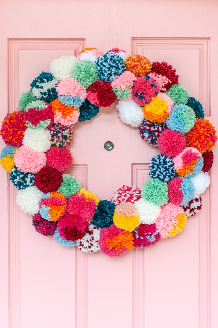 Darling colorful boho popm pom Christmas wreath on a candy pink door for the holidays - Rachel Jacks/Curbly.