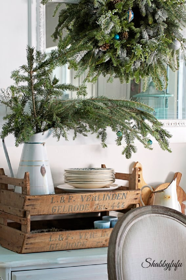 Fresh evergreen branches in a vintage enamel pitcher and rustic wood box make a charming vignette for a Christmas dining room by Shabbyfufu.