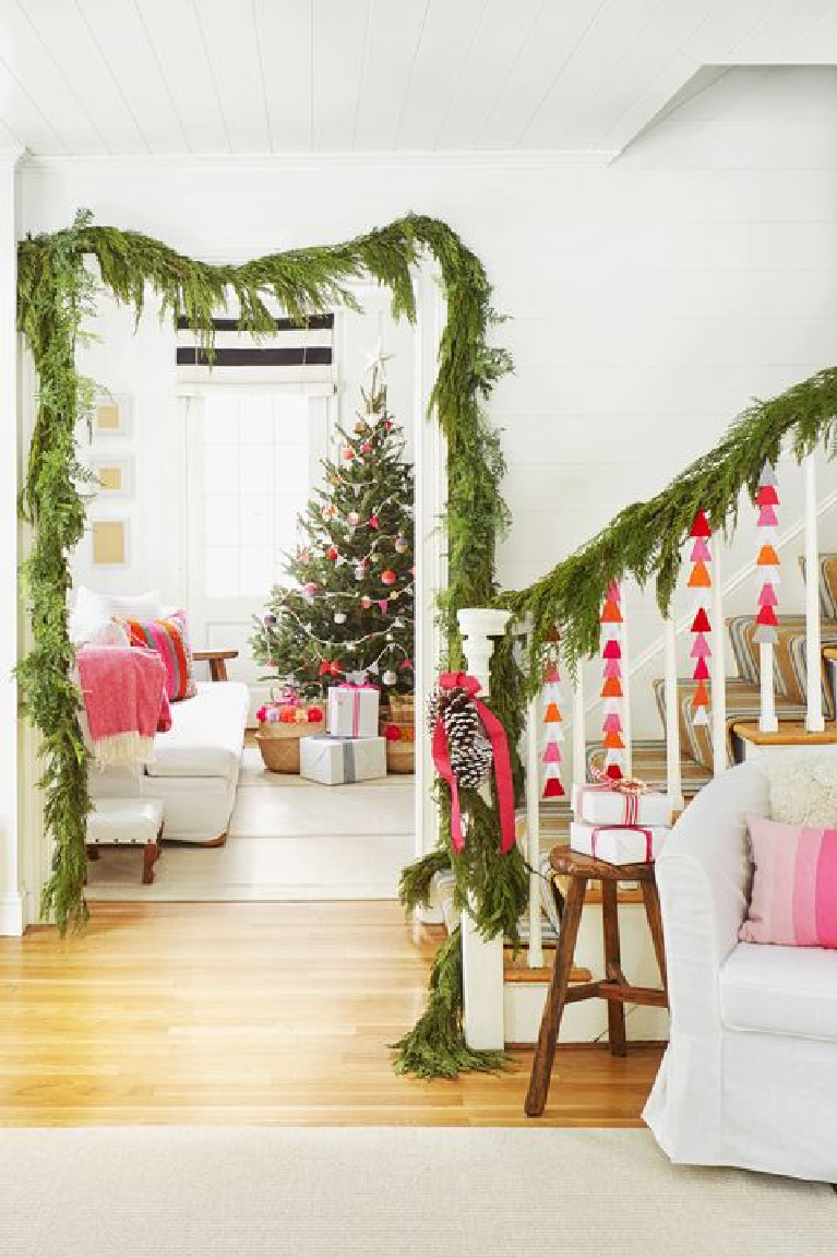 Darling pink Christmas decor accents with fresh greenery in an all white entry and living room with cottage style. #whimsicalchristmas #christmasdecor #shabbychic #countrychristmas