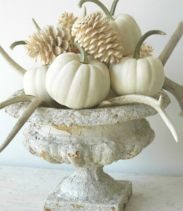 Gorgeous white fall centerpiece with white pumpkins, bleached pinecones, antlers and an old crusty urn - design by Tone on Tone. ##whitepumpkins #babyboo #centerpiece #fallarrangement #tablescape #thanskgiving #centerpiece