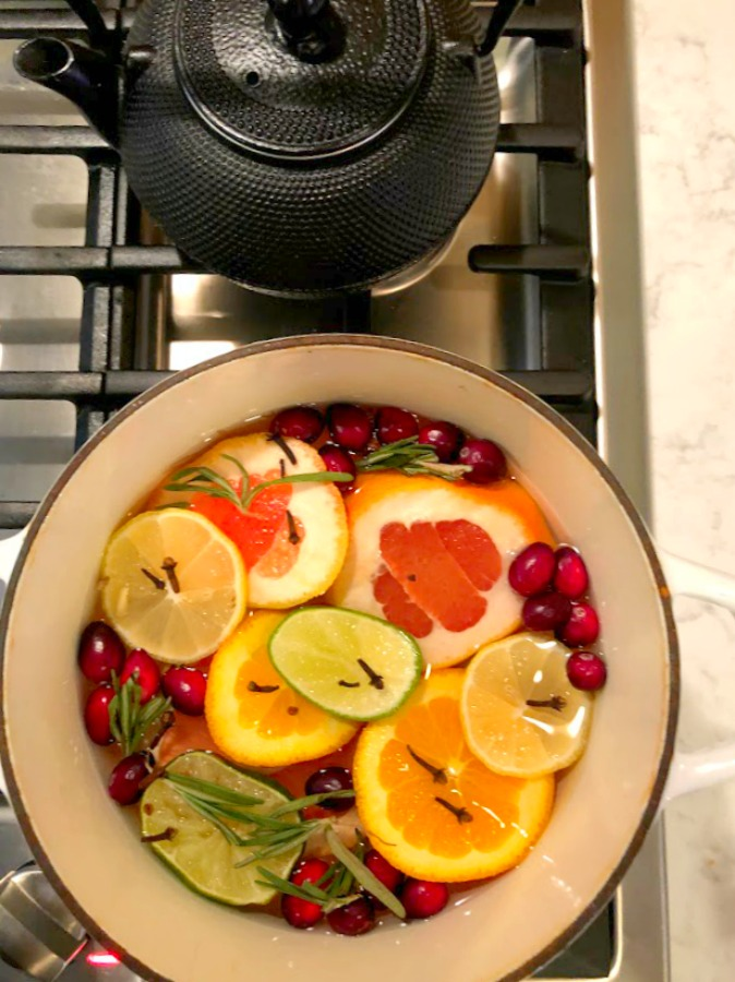 Vividly colorful citrus simmer on the stovetop fragrances the house with grapefruit, rosemary, and fall spices - Hello Lovely Studio.