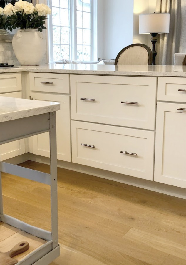 Shaker style white cabinets in simple serene kitchen with white oak floors and Viatera Minuet quartz countertops - Hello Lovely Studio.