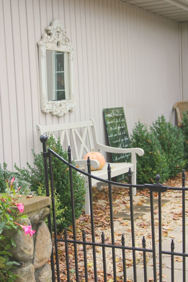 My French inspired courtyard in fall with autumn fallen leaves and boxwood - Hello Lovely Studio.