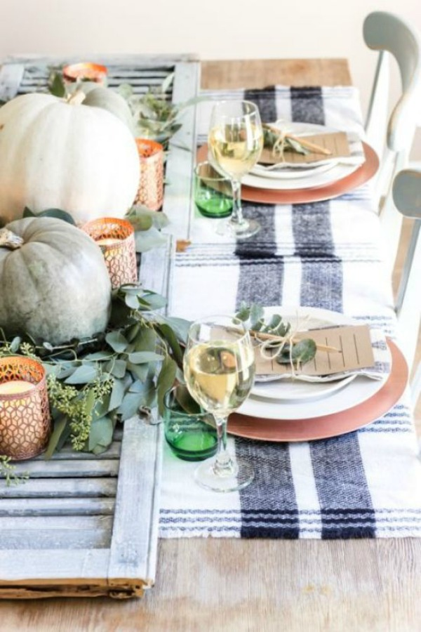 Beautiful rustic farmhouse style Thanksgiving table setting idea with blue stripe linens and pumpkin centerpiece. #thanksgivingtable #tablescape #farmhouse