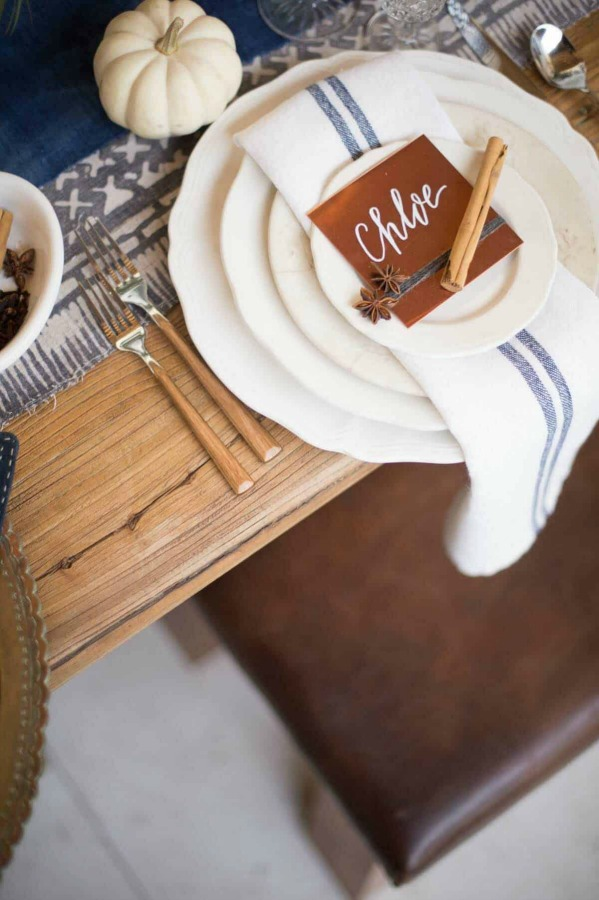 Lovely Thanksgiving table setting idea with blue stripe linen napkins and simple country details - Style Me Pretty. #thanksgivingtable #tablescape #tablesetting #placesetting