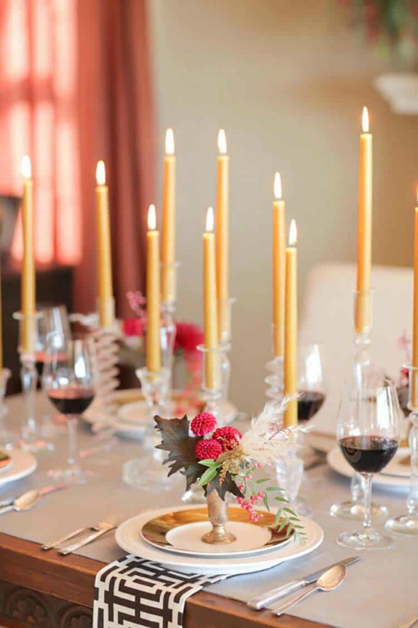 Gorgeously styled Thanksgiving table setting idea with gold toned candles, pink flowers, and crystal candleholders - Camille Styles. #thanksgiving #tablescape #tablesetting #placesetting
