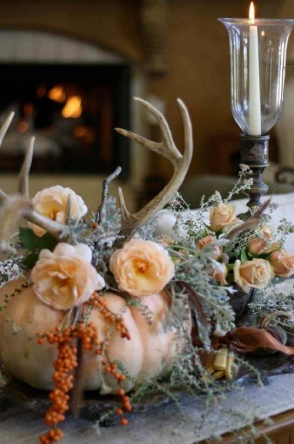 Pumpkin centerpiece with flowers and antlers stars in this Thanksgiving table setting idea. ##thanksgiving #tablescape #pumpkincenterpiece #falltable