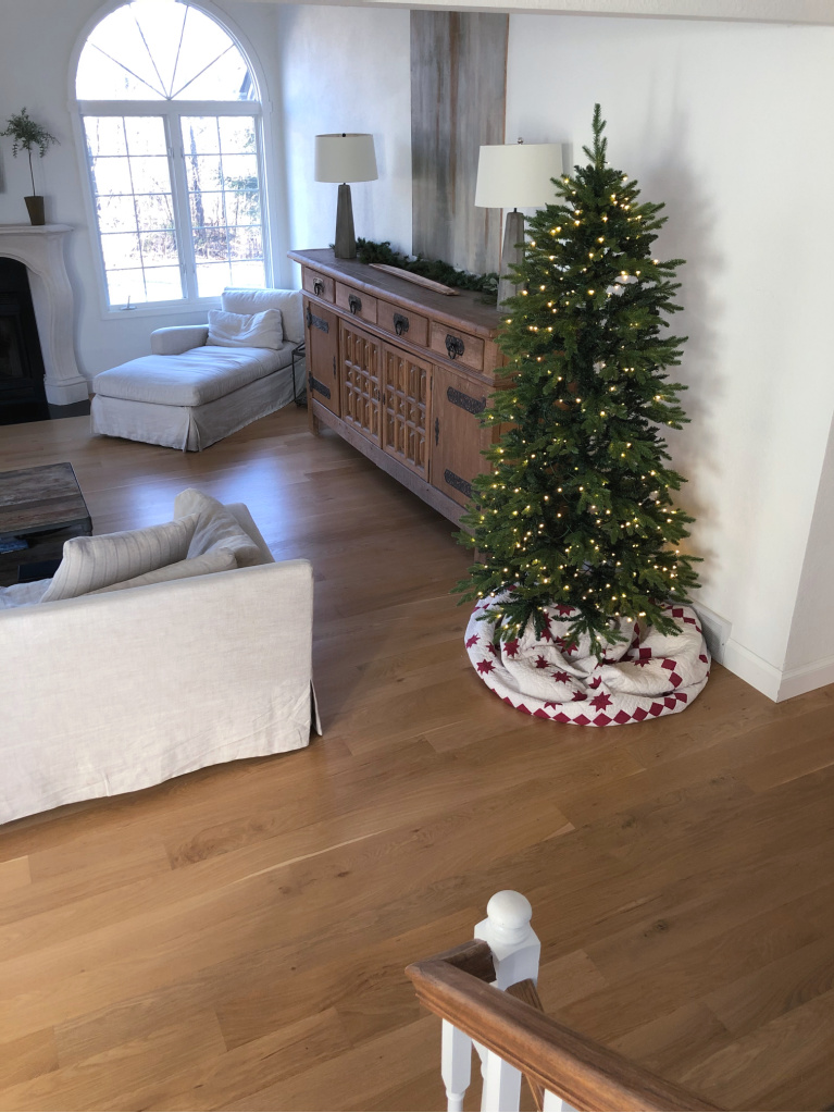 Belgian style living room with Belgian Fir Christmas tree next to antique sideboard - Hello Lovely Studio.