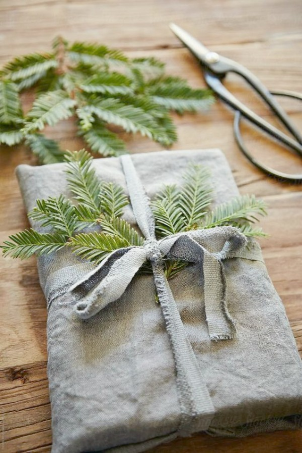 Rustic farmhouse Christmas decor idea with a linen wrapped gift with fresh evergreens - Clem Around the Corner. #christmasdecor #simplechristmas #farmhousechristmas #giftwrap