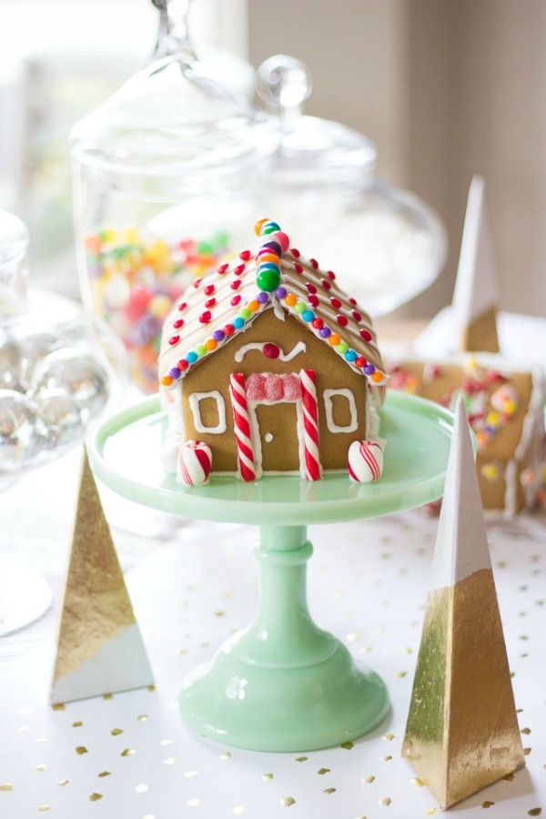 Sweet and petite simple gingerbread house cottage upon a jadeite cake pedestal - Design Improvised. #gingerbreadhouse #christmasdiy #holidaybaking