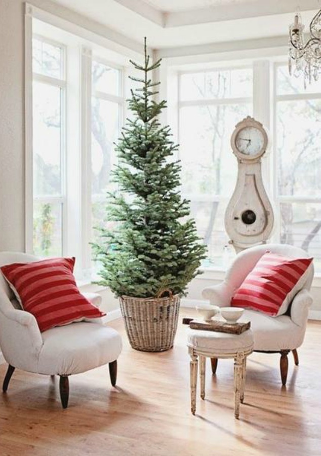 French farmhouse Christmas decor in a living room by Dreamy Whites with Swedish mora clock, tree in vintage basket, and pink stripe pillows. #farmhousechristmas #frenchfarmhouse #holidaydecor #frenchnordicstyle