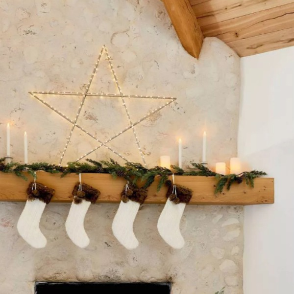 Cozy Christmas mantel with stockings and huge metal star - styling by Emily Henderson for Target. #neutraldecor #whitechristmas #fireplacemantel