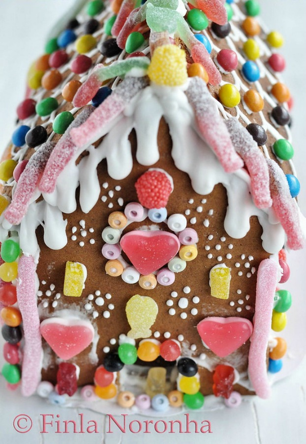 Sweet gingerbread house with fanciful candy decorations by Finla Noronha. #gingerbreadhouse #holidaybaking #christmasdiy