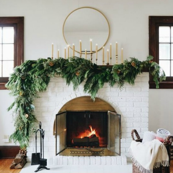 Beautiful faux evergreen garland on white brick holiday fireplace - Francoi et Moi. #fireplace #manteslcape #holidaydecor #garland