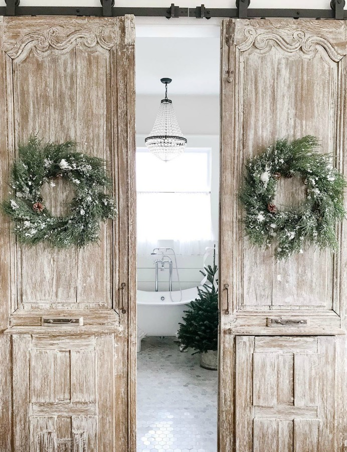 Rustic farmhouse sliding barn doors with Christmas wreaths at entrance to a lovely bath with clawfoot tub - Beside the Mulberry Tree. #farmhousechristmas #christmasdecor #rusticchristmas #countrychristmas #barndoors