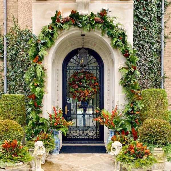 Magnificent French Christmas arched door embellished with at a beautiful chateau in New York - The Enchanted Home. #christmasdecor #elegantdecor #theenchantedhome #frenchchateau #frenchchristmas