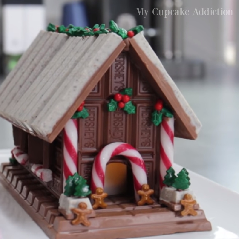Chocolate bar candy gingerbread house with Kitkat and Hershey - MyCupcakeAddiction. #gingerbreadhouses #christmasbaking #candyhouses #chocolatehouses #chocolatelovers #holidaybaking #holidaycrafts