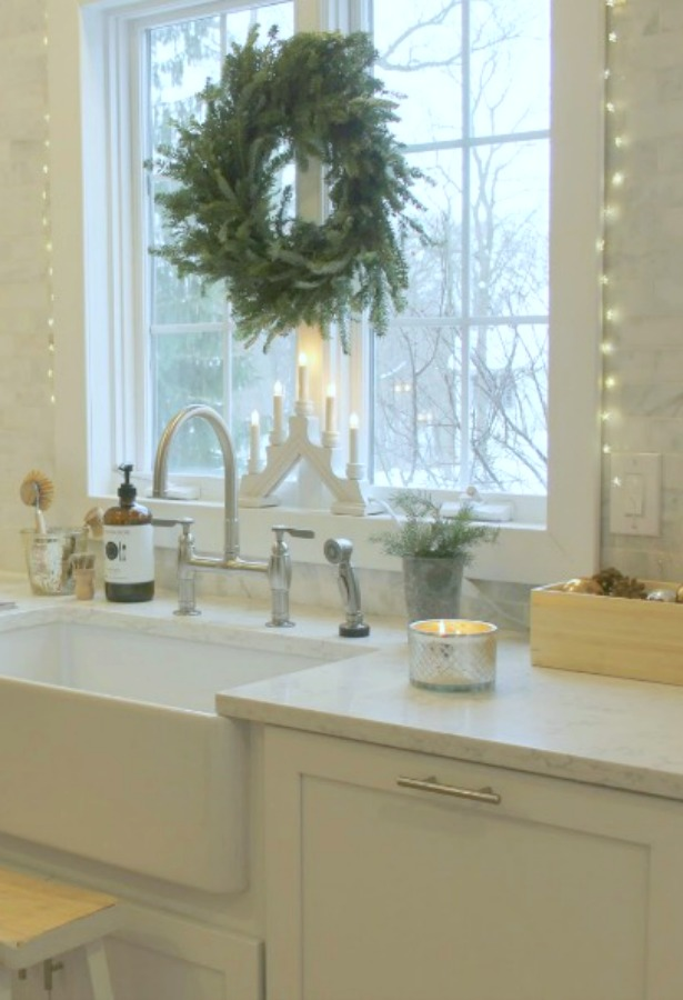 Simple Frasier fir wreath above my farm sink in our white kitchen. #hellolovelystudio #christmasdecor #christmaskitchen
