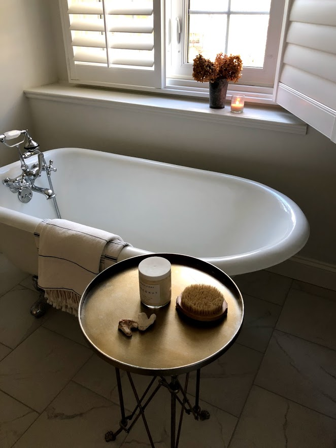Clawfoot tub in a serene white bathroom by Hello Lovely Studio.