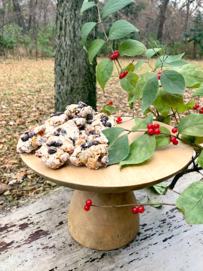 Pistachio Almond Crinkle Cookies on a Wood Pedestal - Hello Lovely Studio. #hellolovelystudio #cookierecipe #pistachio