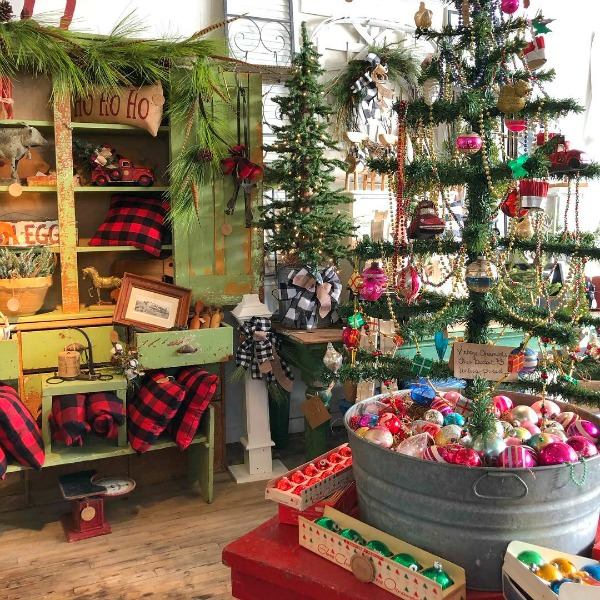 Magnificent vintage Christmas decor inside Trove Vintage with green 1860s cupboard filled with red buffalo check - Hello Lovely Studio. #hellolovelystudio #farmhousechristmas #countrychristmas #christmasdecor #primitives