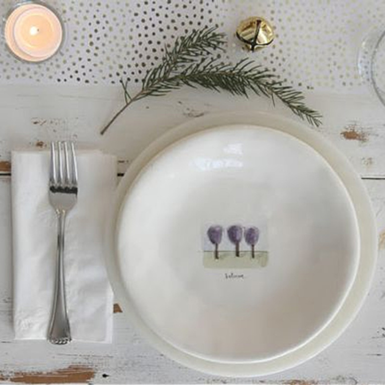 Simple serene holiday placesetting with white Rae Dunn plates and farm table - Hello Lovely Studio. #placesetting #holidaytable #holidaydinner #farmhousechristmas