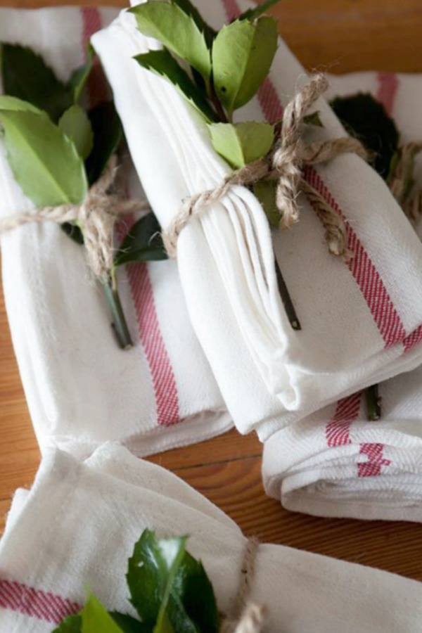 Simple red and white napkins tied with twine and greenery for a holiday tablescape - Ikea. #holidaytable #tablescapes #christmasdecor