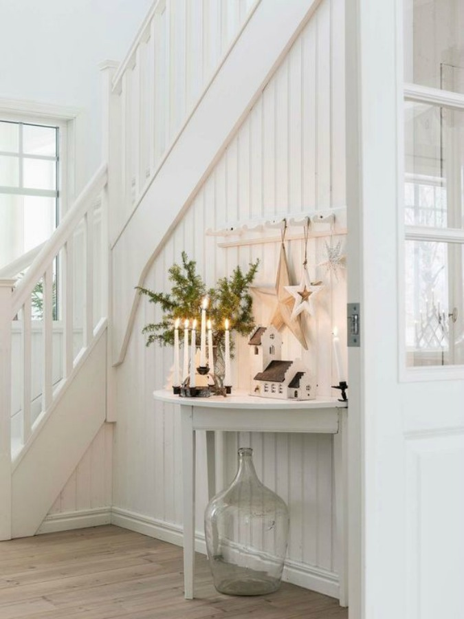 Gorgeous Scandinavian white Christmas decorating in a white cottage style entry with candlelight - Lantliv.