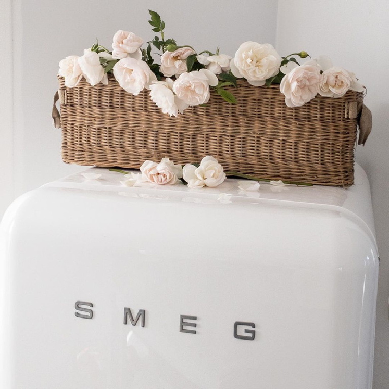 Vintage Smeg refrigerator with antique French basket on top filled with blush pink Francis Meilland roses - My Petite Maison.