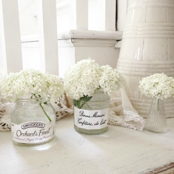 White hydrangea in jam jars in an all white Nordic cottage by My Petite Maison.