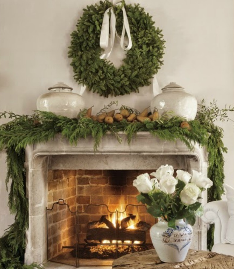 Pamela Pierce Christmas fireplace. She keeps a fire going in the living room and drapes the French period carved stone mantle and surround with mixed garland and olive branches gathered from trees in her yard, interspersed with ripe brown pears. A pair of early Song dynasty jars anchor the scene. White roses are always part of Pam's interior décor.
