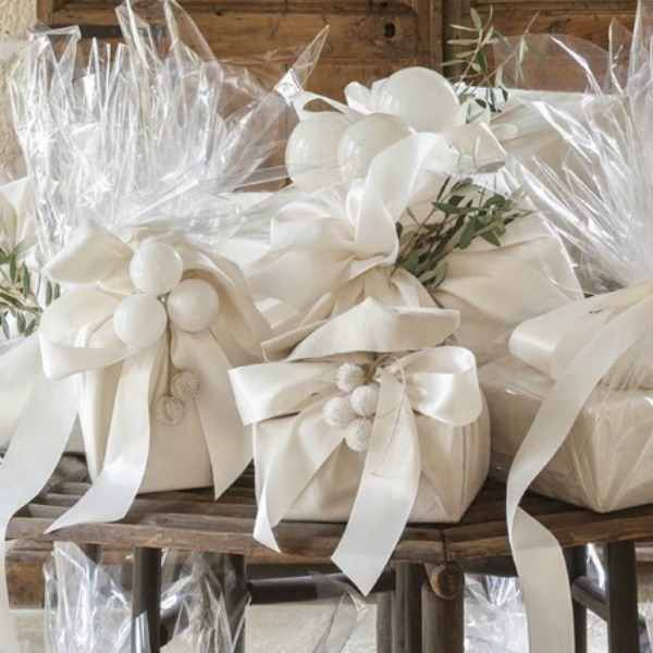 Pamela Pierce Christmas decorated home. Gifts are wrapped in silk chamois and suede cloth. Then the packages are finished with cellophane to create a shimmery sparkle and accented with fresh sprigs from olive branches.