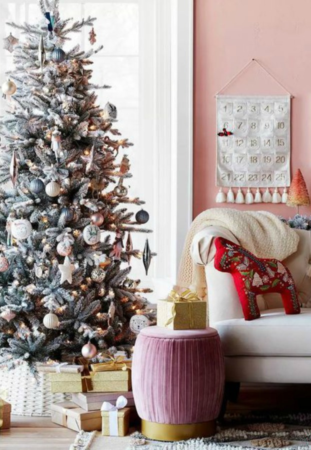Pink Christmas inspiration with pink wall and rose/gold bottle brush tree as well as a pink ottoman - Target.