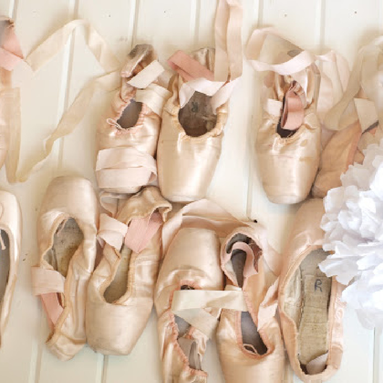 Collection of pale pink pointe shoes with ribbons arranged artfully by Hello Lovely Studio.