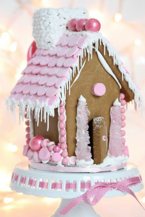 Charming pink accents on a gingerbread house cottage with pink rock candy trees. #gingerbreadhouse #pinkchristmas #holidaybaking